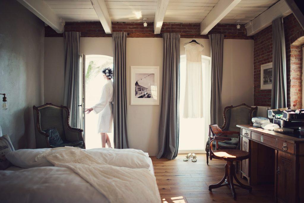 Eine Braut mit Lockenwicklern im Haar schaut aus dem Fenster